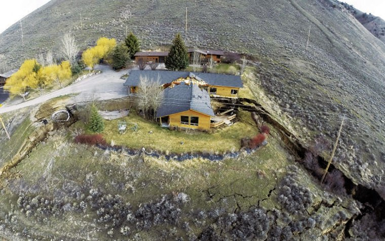A slow-moving landslide split this in two, seen Friday in an aerial image.