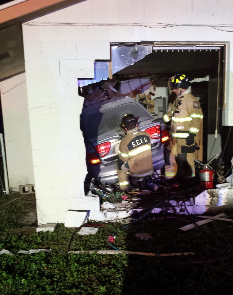 Firefighters work at the scene of a deadly vehicle crash in Sarasota, Fla., on Saturday. A sleeping woman was killed in the house by the crash.