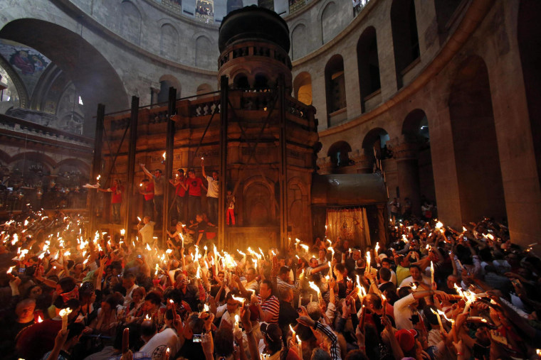 Worshippers hold candles as they take part in the Holy Fire ceremony at the Church of the Holy Sepulchre in Jerusalem's Old City on Saturday.