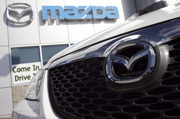 Image: The logo glimmers off the grille of a Mazda vehicle on the lot of a Mazda dealership