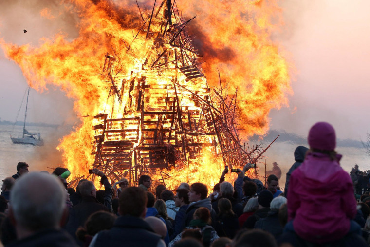 Image: People watch an Easter bonfire next to the river Elbe in Hamburg, Germany