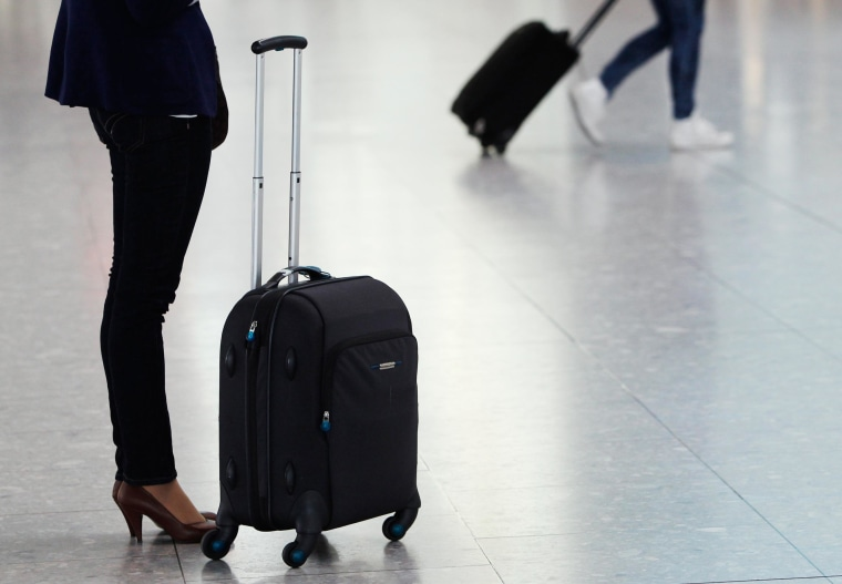 Image: Passengers wait for flights with their luggage at Heathrow airport in London