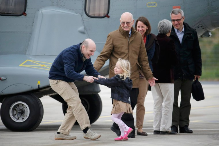 Image: Former French hostage and journalist Nicolas Henin is greeted by his family moments after a transfer by helicopter from Evreux to the military airbase in Villacoublay