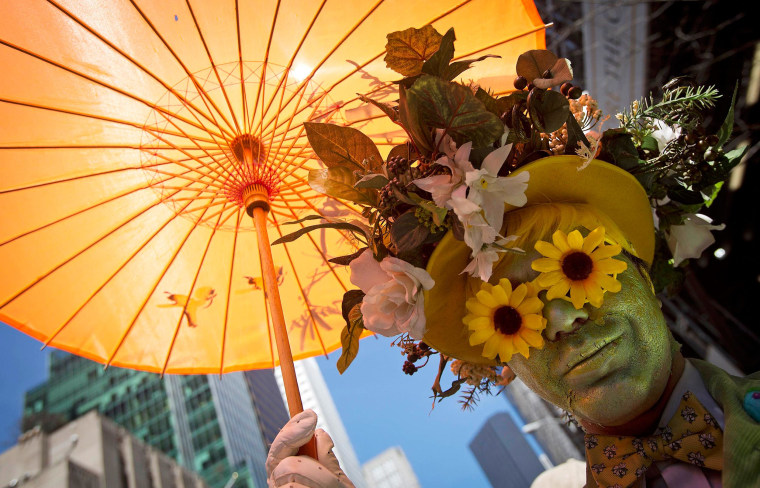 Image: A participant dressed in costume holds an umbrella at the annual Easter Bonnet Parade in New York
