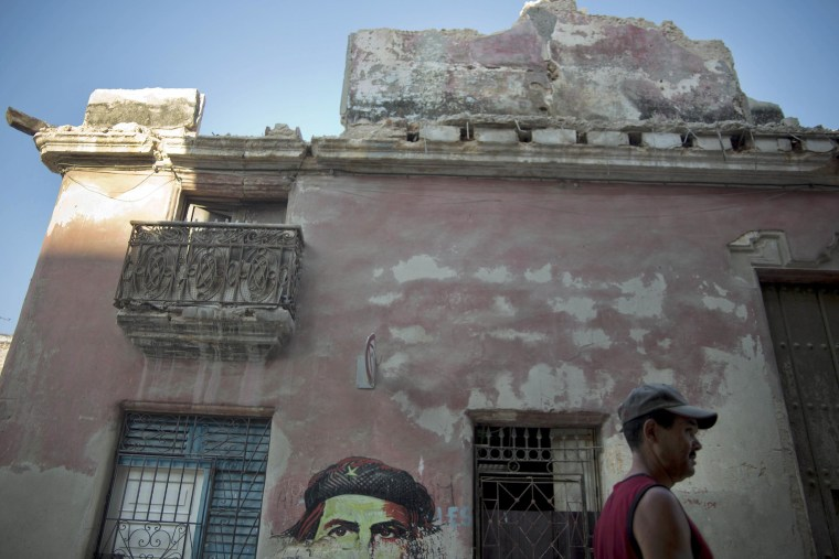 Image: A man walks past a building that collapsed due to the heavy rain next to an image of revolutionary leader Che Guevara in Havana, Cuba