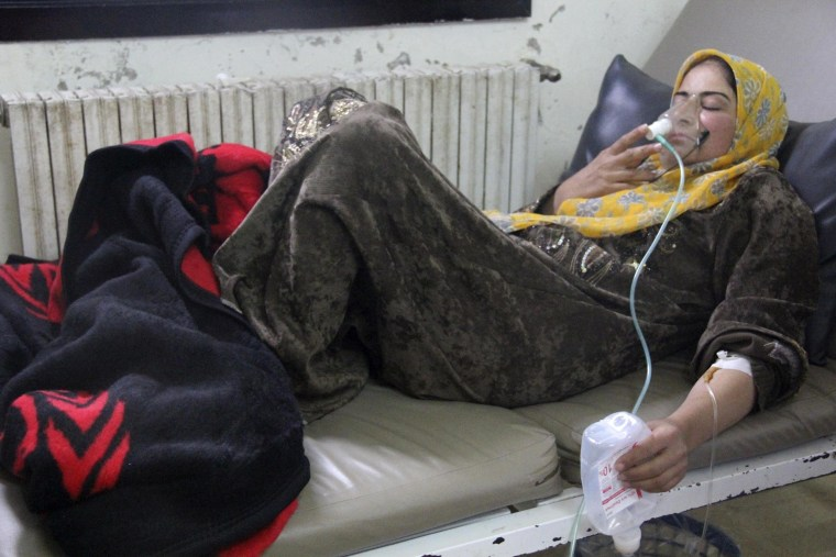 A woman, affected by what activists say was a gas attack, breathes through an oxygen mask inside a field hospital in Kafr Zita, Syria on April 12, 2014. Syrian opposition activists have posted photographs and video that they say shows an improvised chlorine bomb to back up claims that President Bashar al-Assad's forces used chemical weapons in two attacks last week.