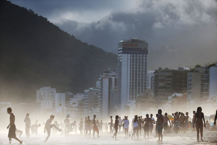 Brazilians play altinha, a spin-off of soccer played on the beach, as others gather on Ipanema Beach in a low-lying mist on April 21, 2014 in Rio de Janeiro, Brazil.