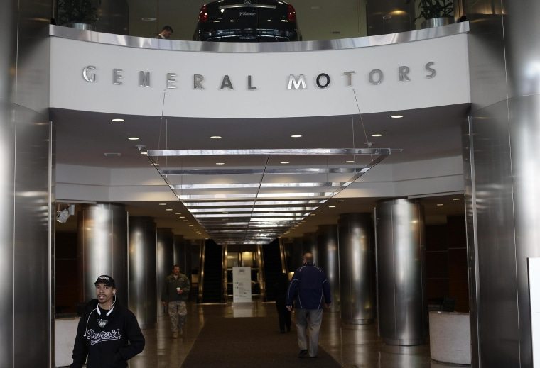 People walk near the front entrance of the General Motors headquarters April 1, 2014 in Detroit, Mich.
