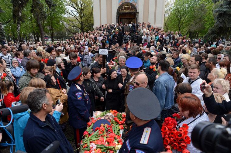 Image: Ukraininan people attend the funeral ceremony of men killed in a gunfight on April 20 in the eastern Ukrainian city of Slovyansk