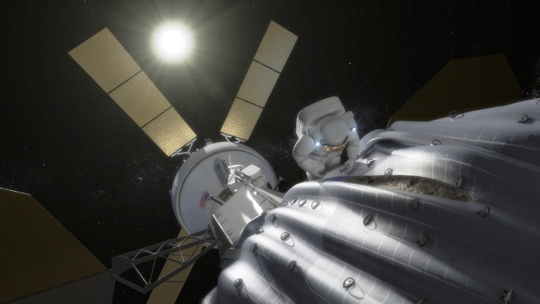 An artist's conception shows an astronaut preparing to take samples from a captured asteroid after it has been relocated to a stable orbit in the Earth-moon system. Hundreds of rings are affixed to the asteroid capture bag, helping the astronaut carefully navigate the surface.