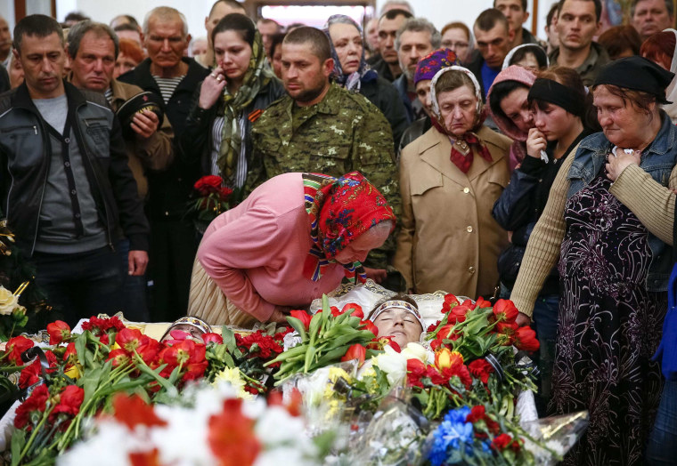 Image: People stand around coffin of man killed in gunfight on April 20 during funeral ceremony in Slaviansk