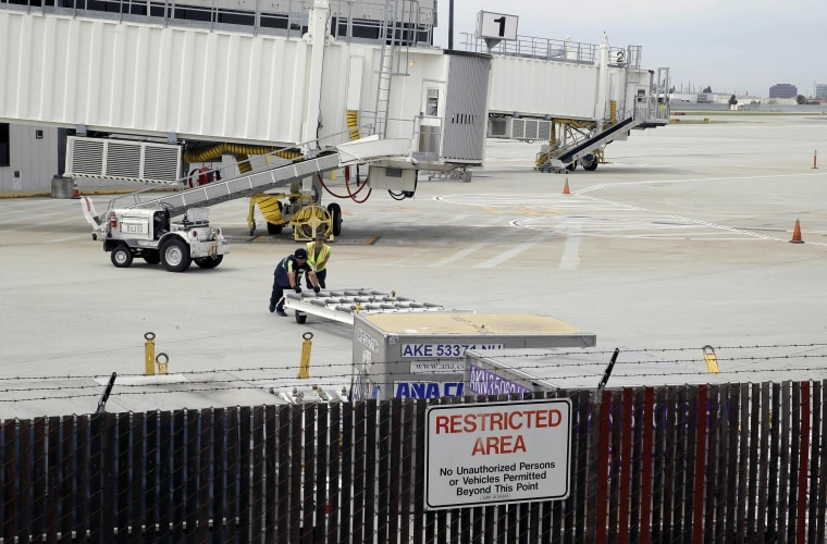 Image:Workers move equipment near gates used by Hawaiian Airlines at Terminal A