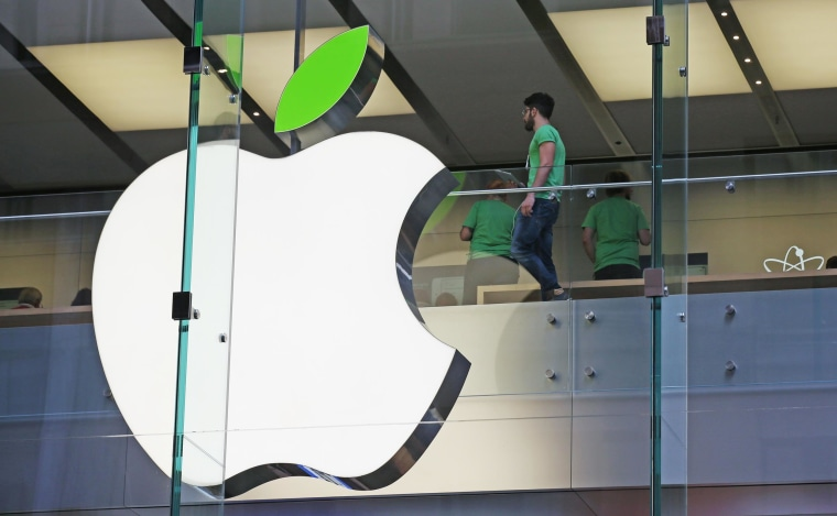Image: Employees wear green shirts near Apple's familiar logo displayed with a green leaf at the Apple Store timed to coincide with Tuesday's annual celebration of Earth Day in Sydney