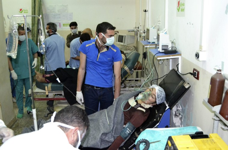 Image: A woman breathes through an oxygen mask at Bab al-Hawa hospital close to the Turkish border