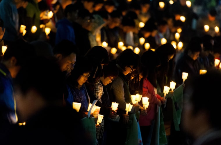 Image: People hold candles at a vigil for missing students who were onboard the South Korean capsized ferry on April 22.