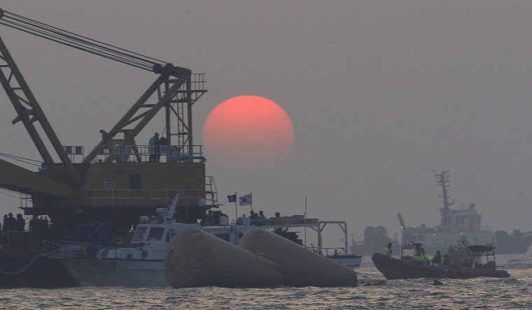 Image: The sun sets as searchers and divers look for bodies of missing passengers onboard the sunken South Korean ferry