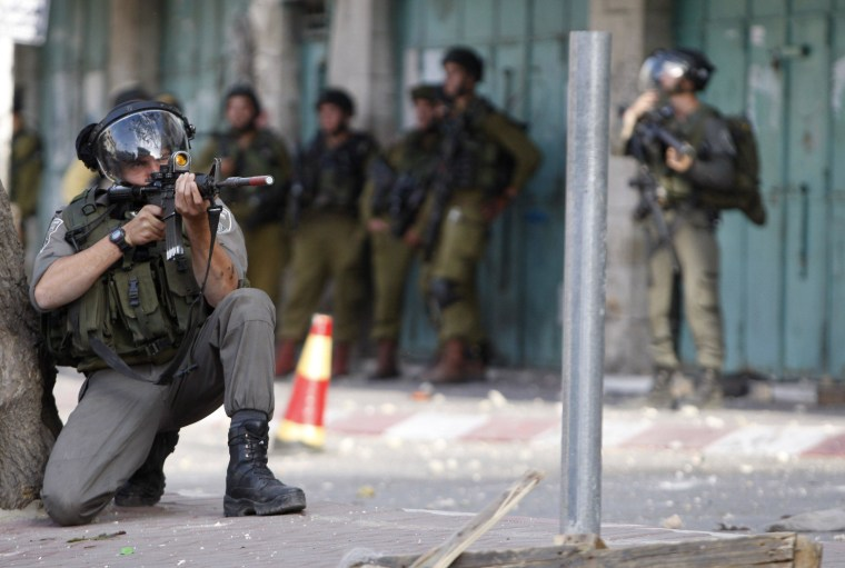 Image: Israeli soldier aims his weapon toward Palestinian stone-throwers during clashes in West Bank city of Hebron