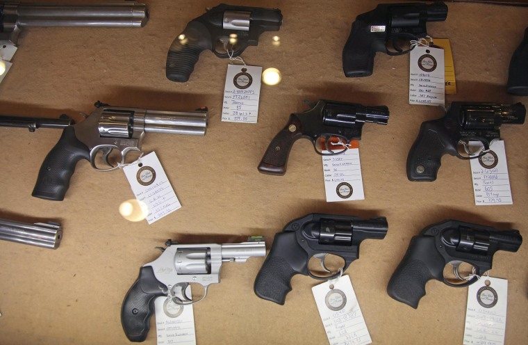 Image: Handguns are displayed in the sales area of a gun range