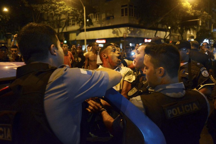 Image: A resident reacts as is detained by the police during a protest against the death of a youth in Pavao-Pavaozinho slum, in Copacabana neighborhood in Rio de Janeiro