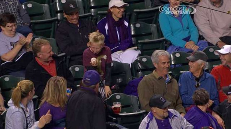 A boy reacts after he was gifted a game ball in the stands at a Giants-Rockies game.