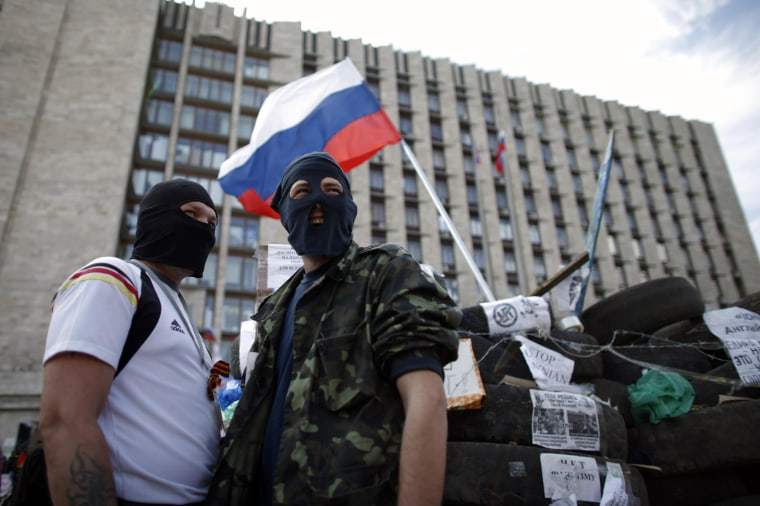 Image: Masked pro-Russia protesters stand guard near a barricade outside a regional government building in Donetsk