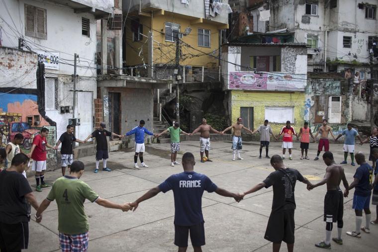 Image: Friends and neighbors of the late Douglas Rafael da Silva Pereira pray before playing soccer in the Pavao Pavaozinho slum of Rio de Janeiro