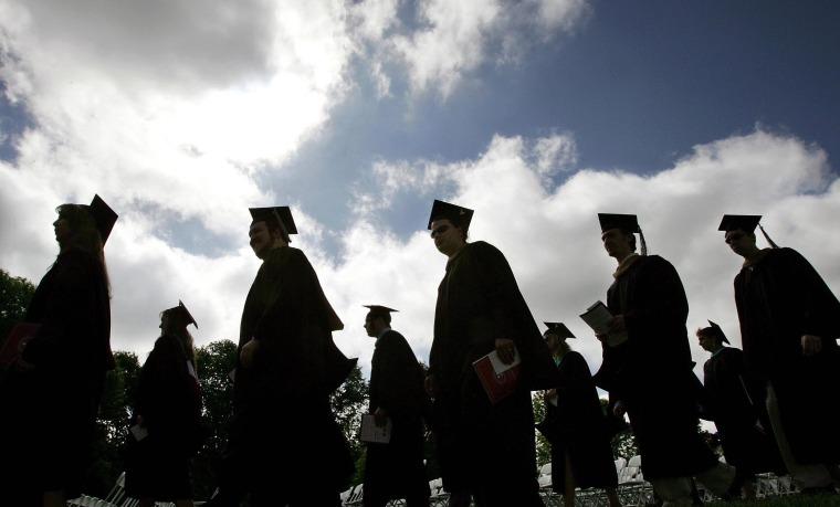 Image: Students in their caps and gowns are silhouetted as they line up for graduation ceremonies.