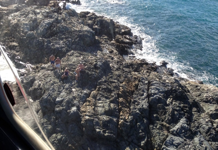 """Five marooned snorkelers were rescued after the huge """"SOS"""" message they scrawled in a sandbar was spotted by a helicopter. The group was winched to safety after their boat broke its anchor and drifted while they were exploring a rocky outcrop off Australi"""