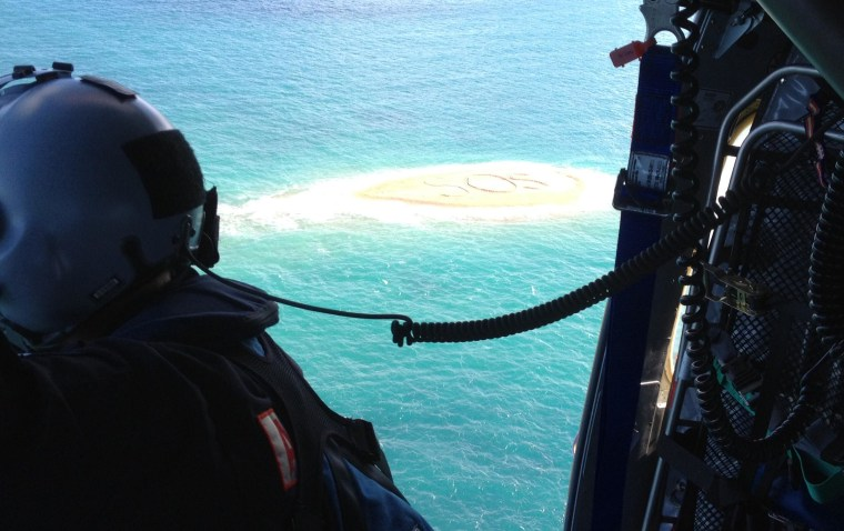 """Five marooned snorkelers were rescued after the huge \""""SOS\"""" message they scrawled in a sandbar was spotted by a helicopter. The group was winched to safety after their boat broke its anchor and drifted while they were exploring a rocky outcrop off Australi"""