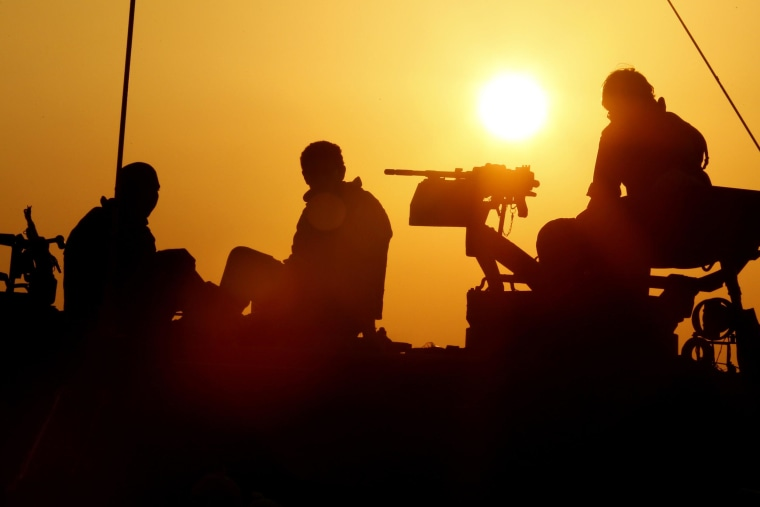Israeli soldiers sit on top of amobile artillery canon unit near the Israel-Gaza Strip border.