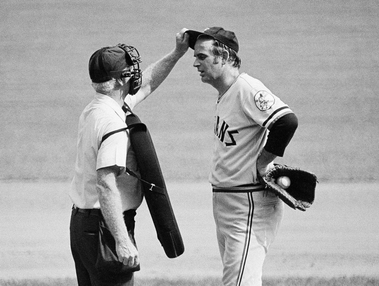 Home plate umpire John Flaherty checks Cleveland Indians' pitcher Gaylord Perry's cap, at the request of Milwaukee Brewers manager Del Crandall, during the first game of a doubleheader against the Brewers in Milwaukee on Sept. 3, 1973.