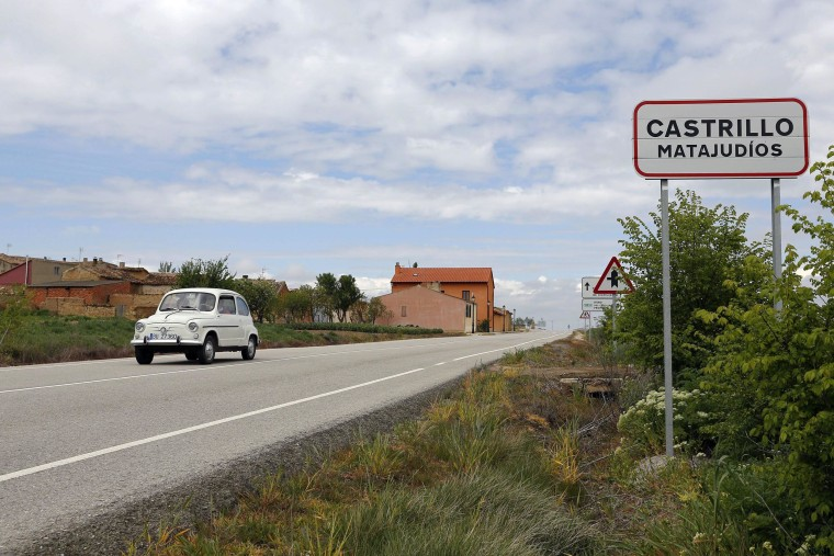 Image: A car passes by the road sign at the entrance of the small Spanish town of Castrillo Matajudios