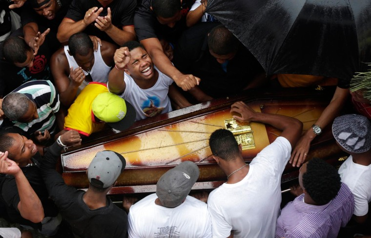 Image: Relatives and friends of Douglas Rafael da Silva Pereira, 25, mourn during his burial in Rio de Janeiro