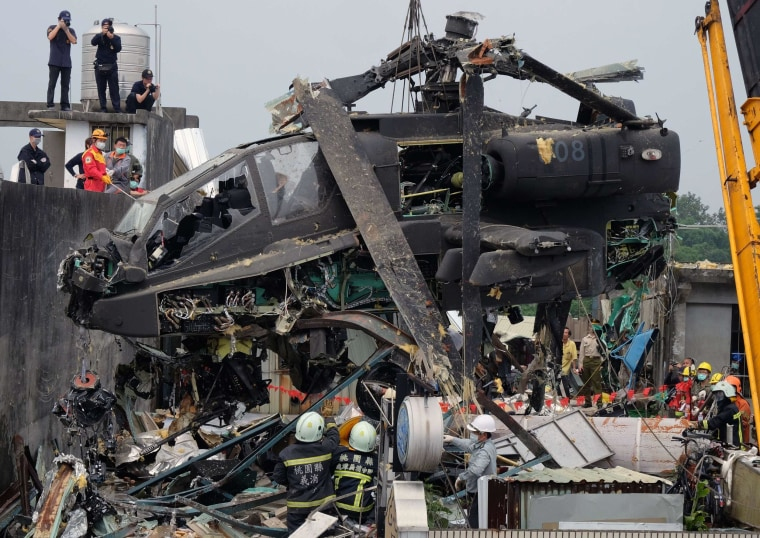 Image: Workers lift a damaged U.S.-made AH-64E Apache attack helicopter from a roof in Taoyuan, northern Taiwan