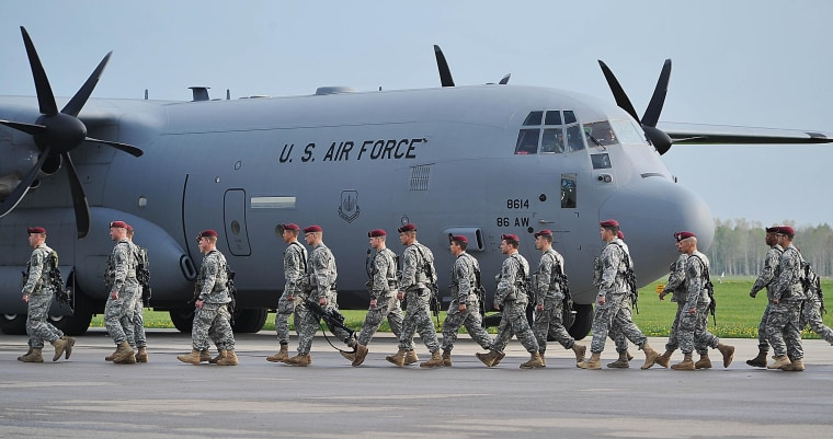 U.S. paratroopers are walking on the tarmac after being flown into the air base in Swidwin, Poland, Wednesday, April 23, 2014 for weeks of joint exercise. Their arrival was requested by Poland as a way of increasing security at a time of conflict between two of its neighbors, Ukraine and Russia. (AP Photo/Lukasz Szelemej)