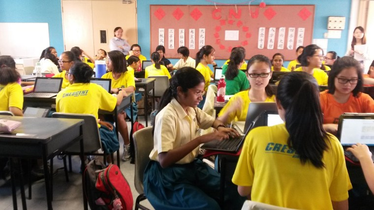 Students at Crescent Girls School in Singapore discuss conflict and discrimination in groups while working on a shared Google Doc.