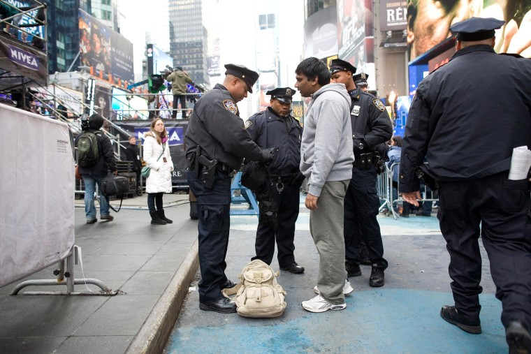 New York City Police Department officers search the bag of a man in Times Square.