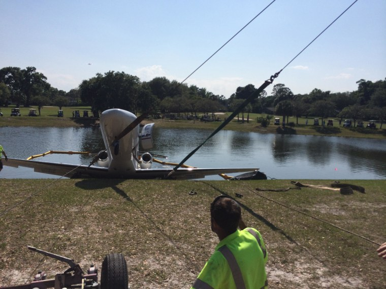 Image: A worker looks on as a plane is towed out of a pond in Volusia County, Fla.