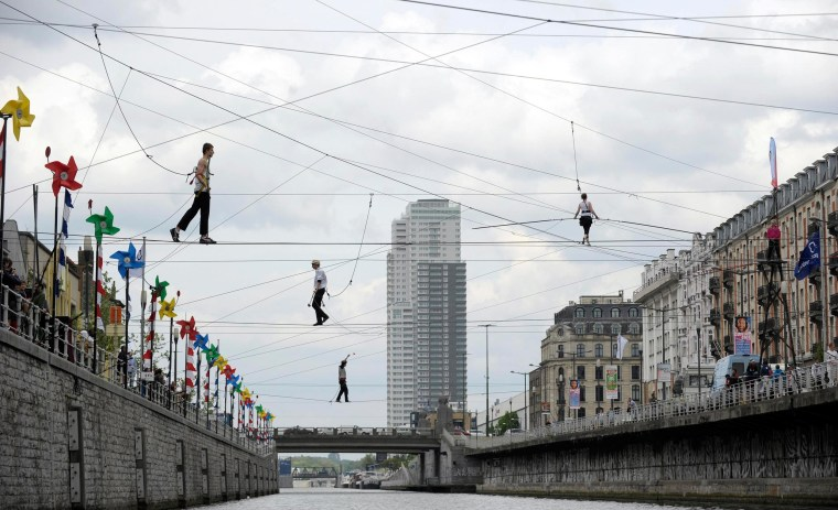 Image: Tightrope walkers perform above a canal in Brussels