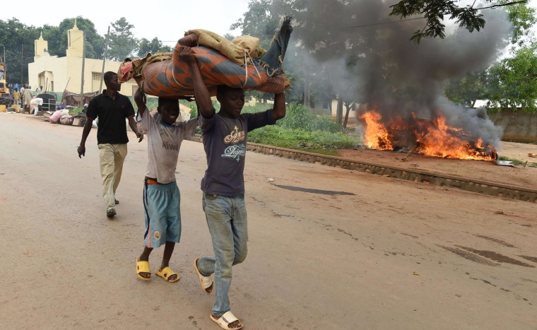 Image: Children carry furniture as they walk past a burning car outside Bangui