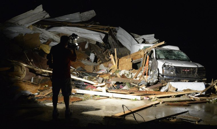 A videographer covers the damage after a tornado hit the town of Mayflower, Arkansas around 7:30 pm CST, late April 27, 2014. Tornadoes ripped through the south-central United States on Sunday, killing at least 12 people in Arkansas and Oklahoma and wiping out entire neighborhoods of homes, according to officials, as rescue workers searched in darkness for survivors. In Mayflower, some of about 45 homes were destroyed in a newer subdivision and a lumberyard was damaged, said Will Elder, an alderman in the city of 2,300 people. REUTERS/Gene Blevins (UNITED STATES - Tags: ENVIRONMENT DISASTER MEDIA)