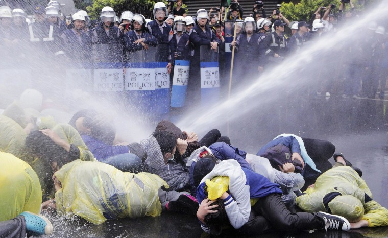 Police use a water cannon to disperse demonstrators protesting the construction of a fourth nuclear plant, in front of Taipei Railway station in Taipei April 28, 2014.
