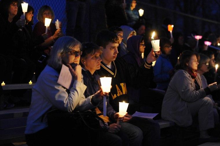 Image: People raise candles at a vigil for Maren Sanchez