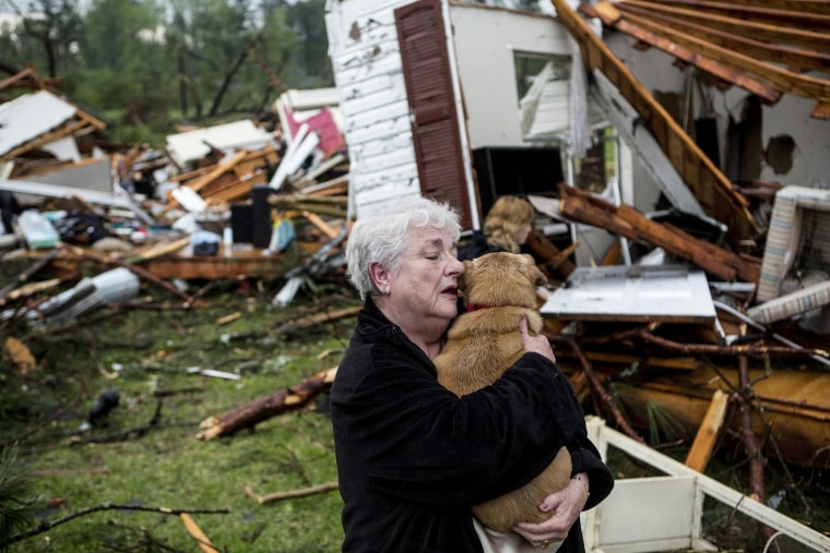 Image: Constance Lambert embraces her dog after finding it alive when returning to her destroyed home in Tupelo