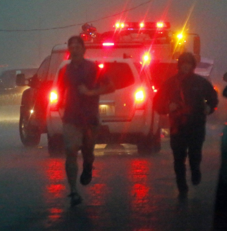 Image: A volunteer joins a first responder after a tornado hit Louisville, Miss.