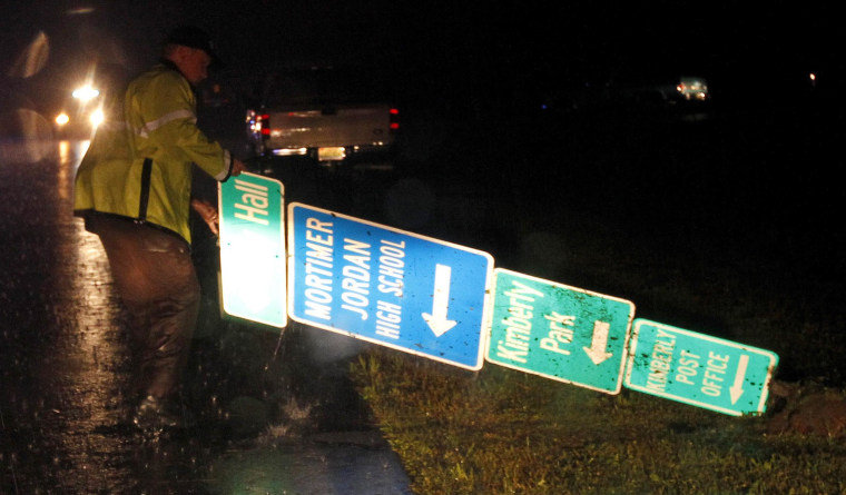 An officer moves a sign from the road after a possible tornado passed through, damaging homes and business on Monday, April 28, in Kimberly, Ala.