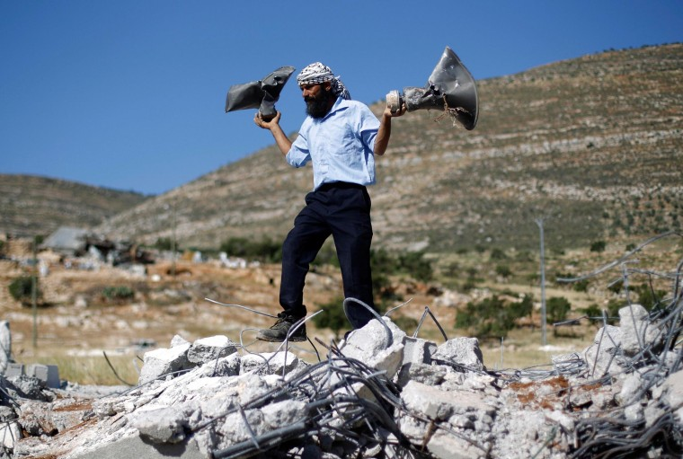 Image: A Palestinian man holds damaged loudspeakers belonging to a mosque after it was demolished by Israeli bulldozers in Khirbet al-Taweel village