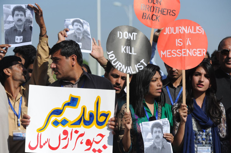 Image: Pakistani journalists hold placards and photographs bearing the image of colleague Hamid Mir