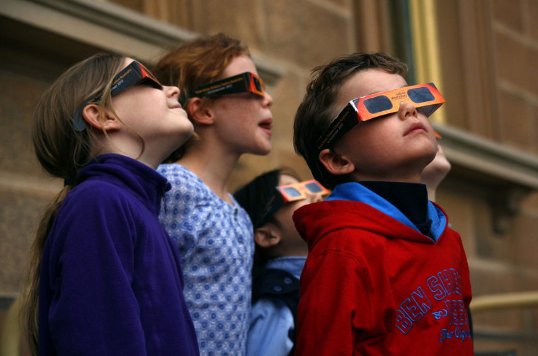 Image: Children wear protective glasses as they try to see a partial solar eclipse from Sydney's Observatory Hill