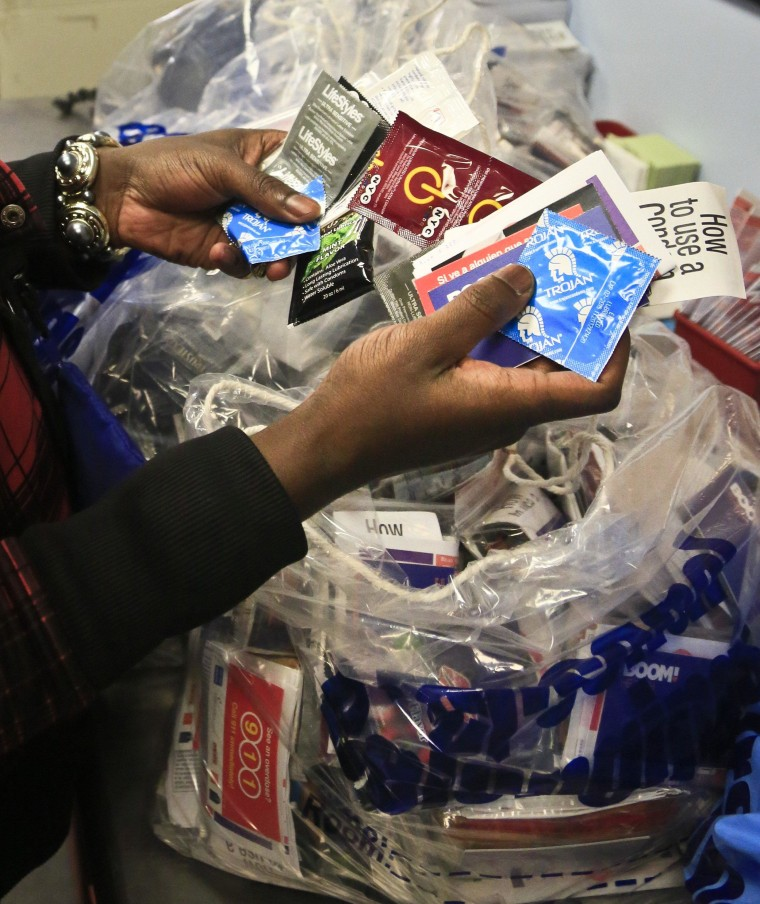 J. Starks, an outreach worker at Boom Health center, package condoms for distribution to sex trade workers, Friday April 25, 2014 in Bronx, N.Y.  City police are allowed to confiscate those very condoms as evidence of prostitution, yet New York City spends more than a million dollars every year to distribute free condoms to combat unintended pregnancies and diseases.  That conflict is behind the latest legislative proposal to prohibit condoms from being used as evidence in prostitution cases.